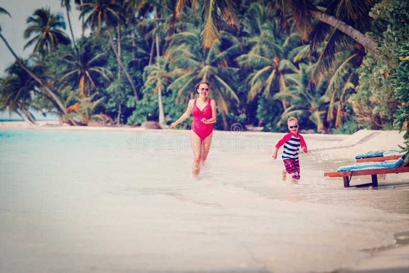 Moeder en zoon die in water op strand lopen stock fotografie