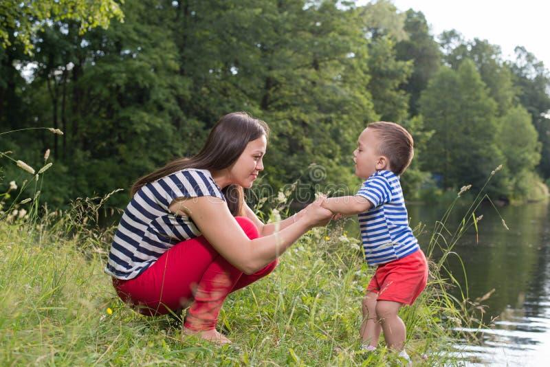 Moeder en zoon in het park dichtbij meer royalty-vrije stock foto