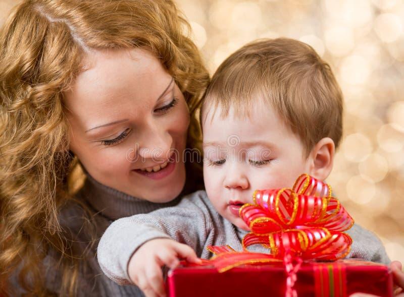 Moeder en zoon met gift over festivalachtergrond stock afbeelding