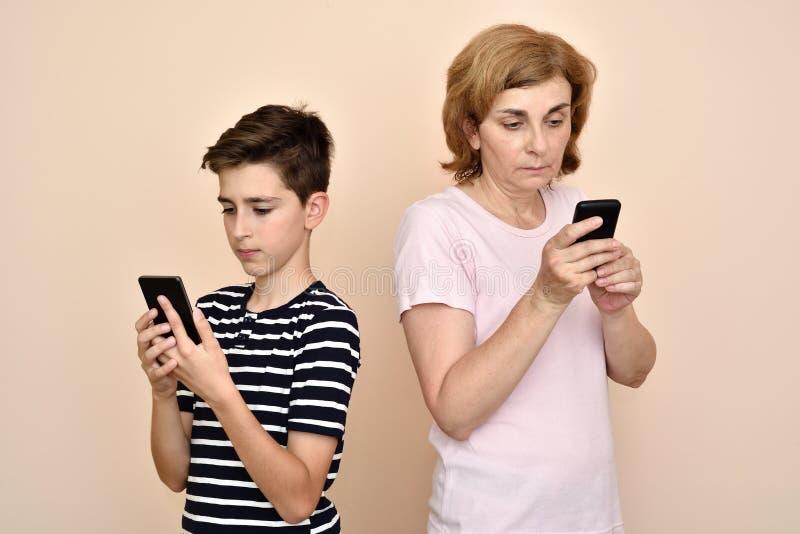 Moeder en zoon met hun smartphones royalty-vrije stock fotografie