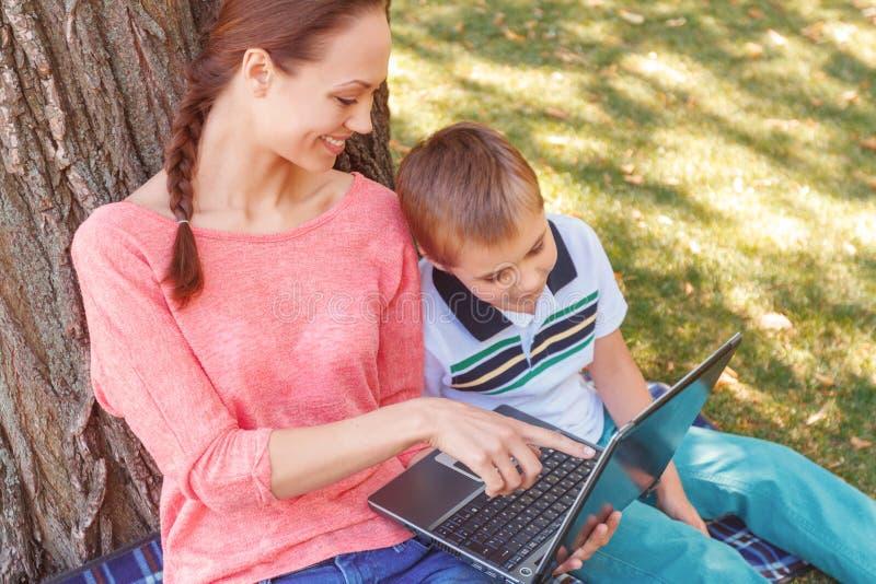 Moeder en zoon met laptop op picknick royalty-vrije stock afbeelding
