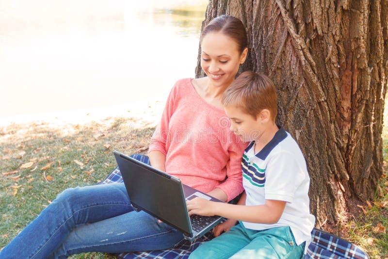 Moeder en zoon met laptop op picknick stock fotografie