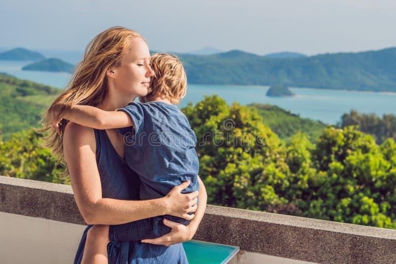 Moeder en zoon op de achtergrond van het Tropische panorama van het strandlandschap De mooie turkooise oceaan schort met boten op stock afbeeldingen