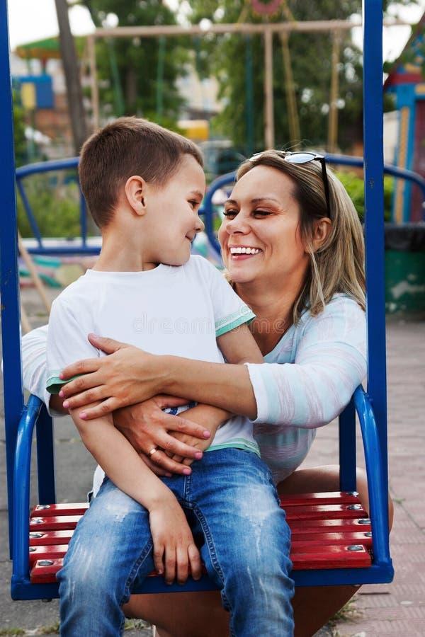 Moeder en zoon op de speelplaats stock foto