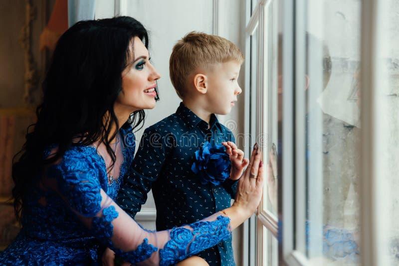 Moeder en zoon samen dichtbij groot venster royalty-vrije stock foto
