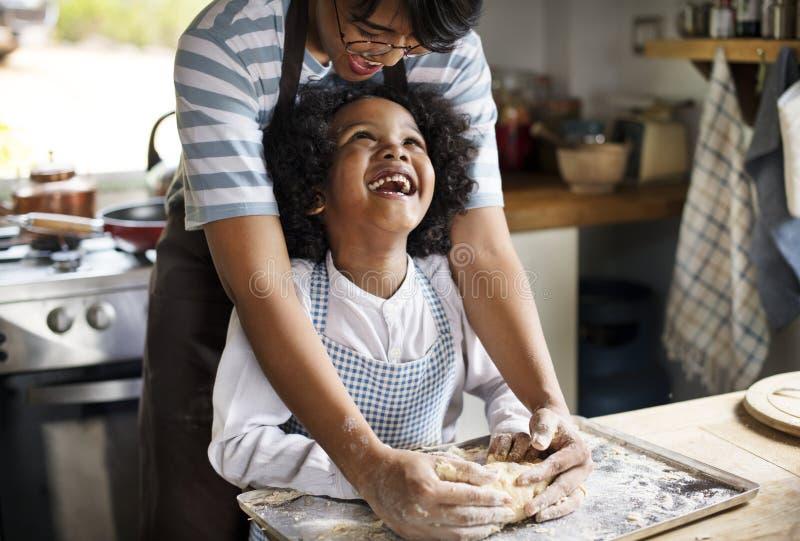 Moeder en zoons het kneden deeg in de keuken royalty-vrije stock afbeelding