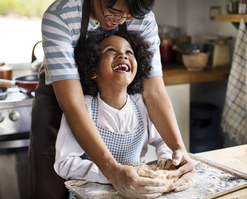Moeder en zoons het kneden deeg in de keuken royalty-vrije stock foto