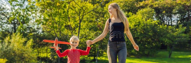 Moeder en zoons het spelen met een groot modelstuk speelgoed vliegtuig in de parkbanner, LANG FORMAAT stock afbeeldingen