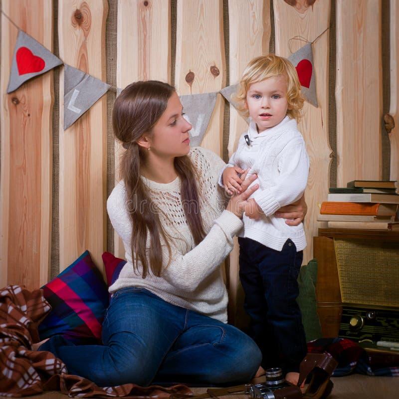 Moeder en zoons het spelen op de vloer in een buitenhuis stock afbeelding