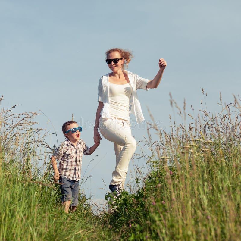 Moeder en zoons het spelen op het park in de dagtijd stock fotografie
