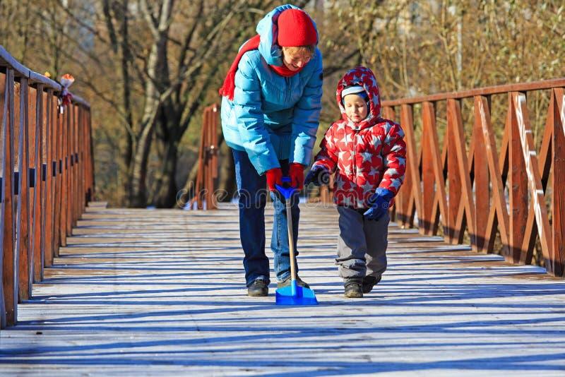 Moeder en zoons schoonmakende sneeuw in openlucht royalty-vrije stock fotografie