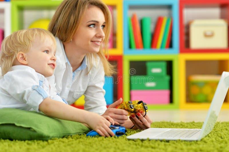 Moeder en zoons speelcomputerspel met laptop stock fotografie