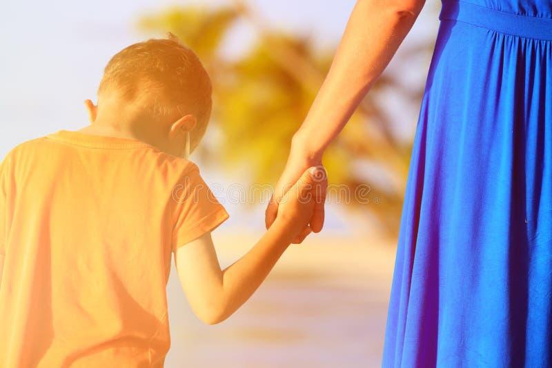 Moeder en zoonsholdingshanden op strand stock afbeeldingen