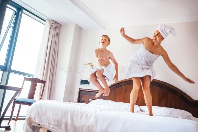 Moeder en zoonssprong op bed in de ruimte van het luxehotel royalty-vrije stock afbeeldingen