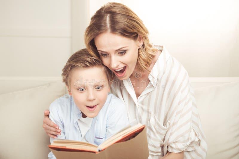 Moeder en zoonszitting die en boek samen omhelzen lezen stock fotografie