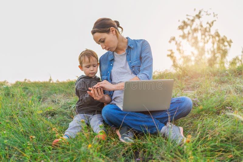 Moeder en zoonszitting op het gras royalty-vrije stock fotografie