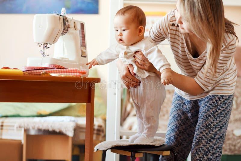 Moeder en zuigeling, huis, de baby eerste stappen, natuurlijk licht Kinderverzorging met het werk thuis wordt gecombineerd dat stock afbeeldingen