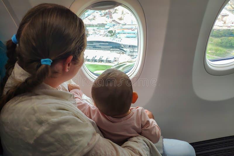 Moeder en zuigelingsbaby in het vliegtuig dichtbij het venster De blik op de grond en geniet van de vlucht stock fotografie