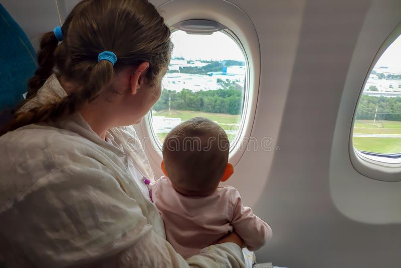 Moeder en zuigelingsbaby in het vliegtuig dichtbij het venster De blik op de grond en geniet van de vlucht Reis met onder kindere stock fotografie