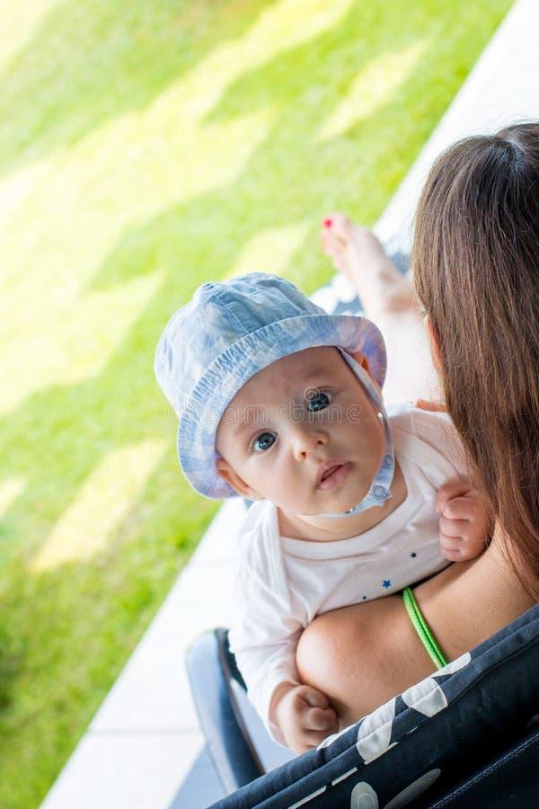 Moeder gevend kind buiten bij portiek, babygezicht die interessant kijken stock afbeelding