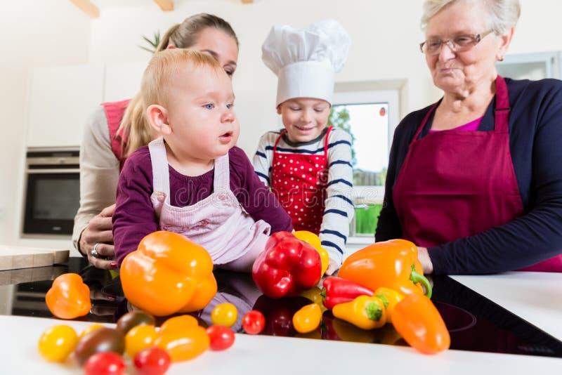 Moeder, grootmoeder en kinderen die maaltijd in keuken voorbereiden royalty-vrije stock afbeeldingen