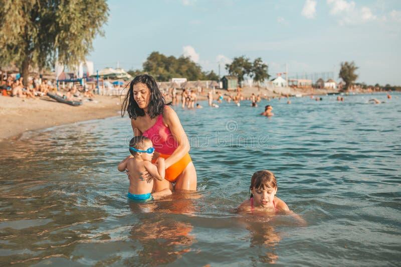 Moeder, haar weinig zoon en dochter die pret in het water maken stock foto