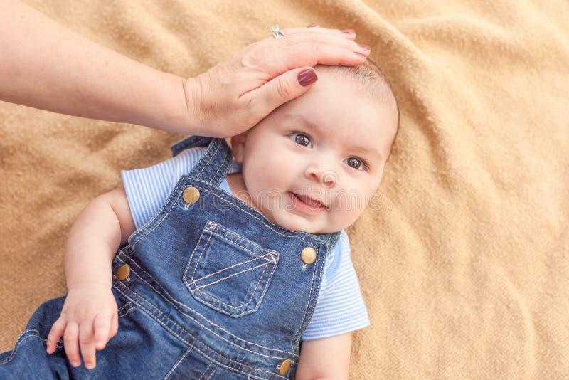 Moeder Hand op een Happy Mixed Race Baby Boy Laying op Blanket stock afbeeldingen