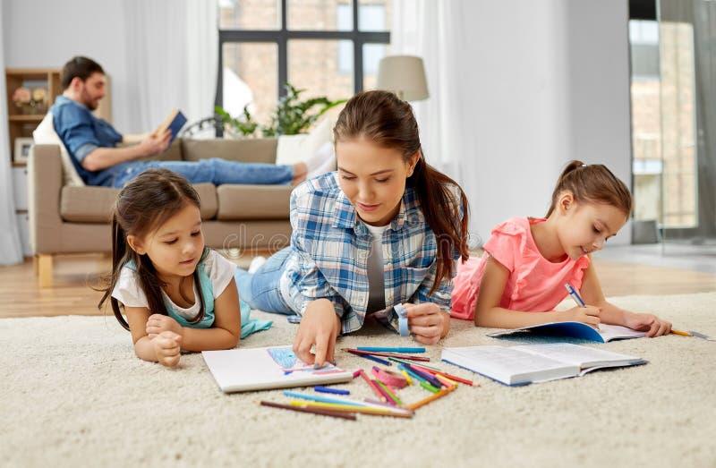 Moeder het besteden tijd met kleine dochters thuis stock afbeelding