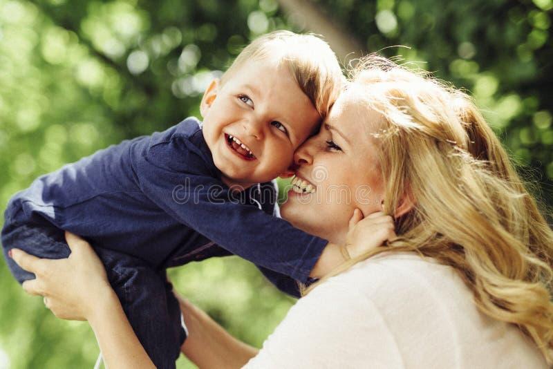 Moeder het glimlachen in openlucht lachend en spelend met haar kind stock foto