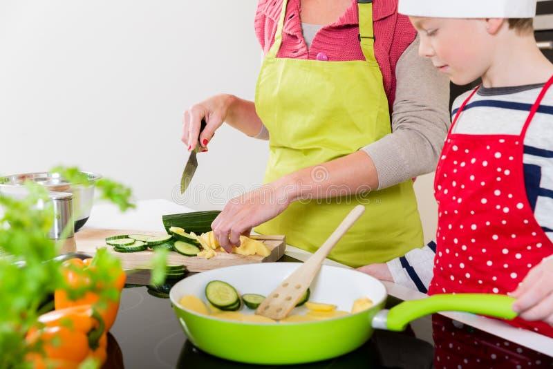 Moeder het koken in de keuken, zoon het letten op royalty-vrije stock foto