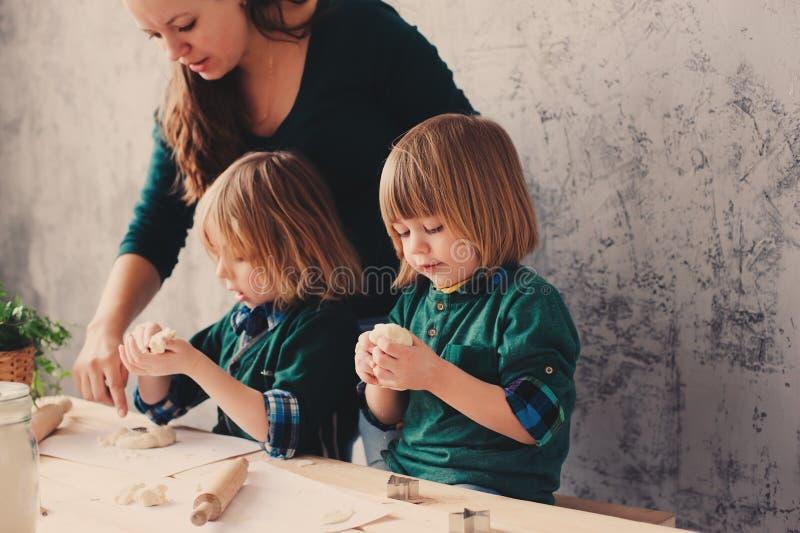 Moeder het koken met jonge geitjes in keuken Peutersiblings die samen en met gebakje thuis spelen bakken royalty-vrije stock afbeeldingen