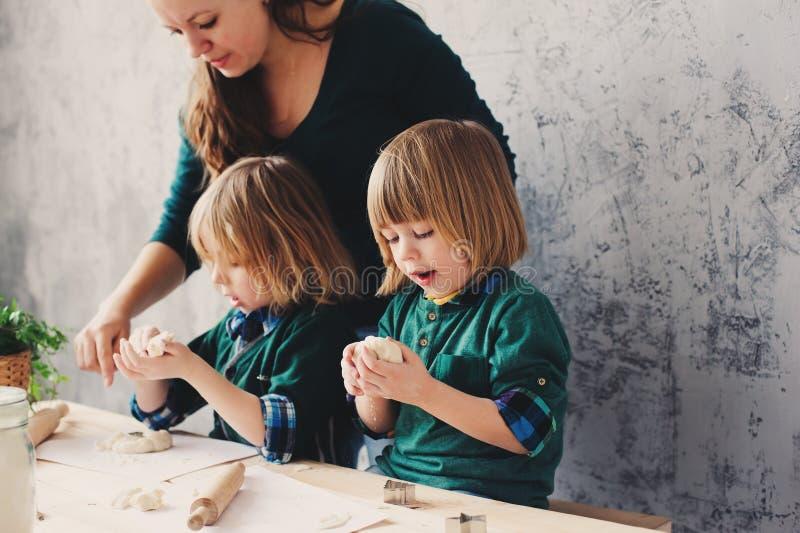 Moeder het koken met jonge geitjes in keuken Peutersiblings die samen en met gebakje thuis spelen bakken stock afbeeldingen