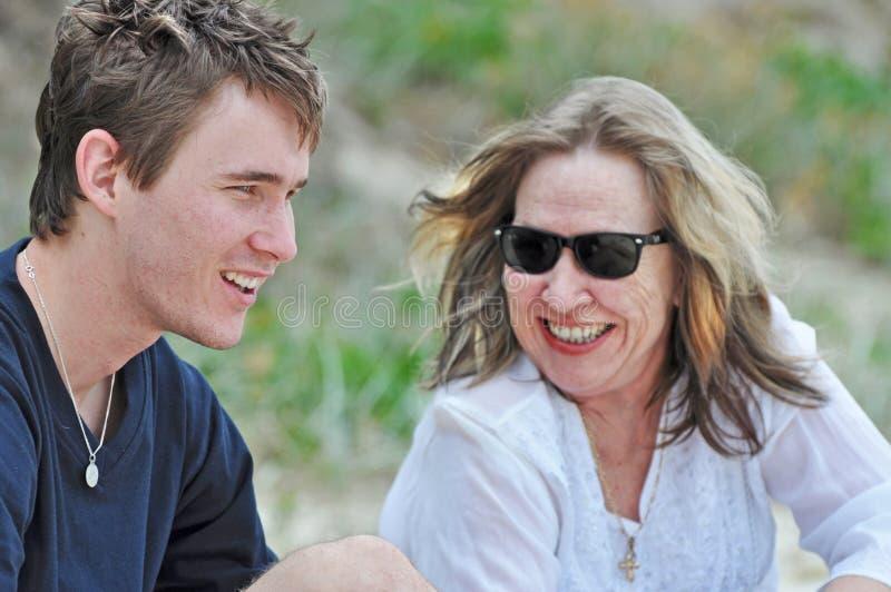 Moeder het lachen het glimlachen het houden van delend tijd met zoon op de vakantie van het de zomerstrand royalty-vrije stock afbeeldingen