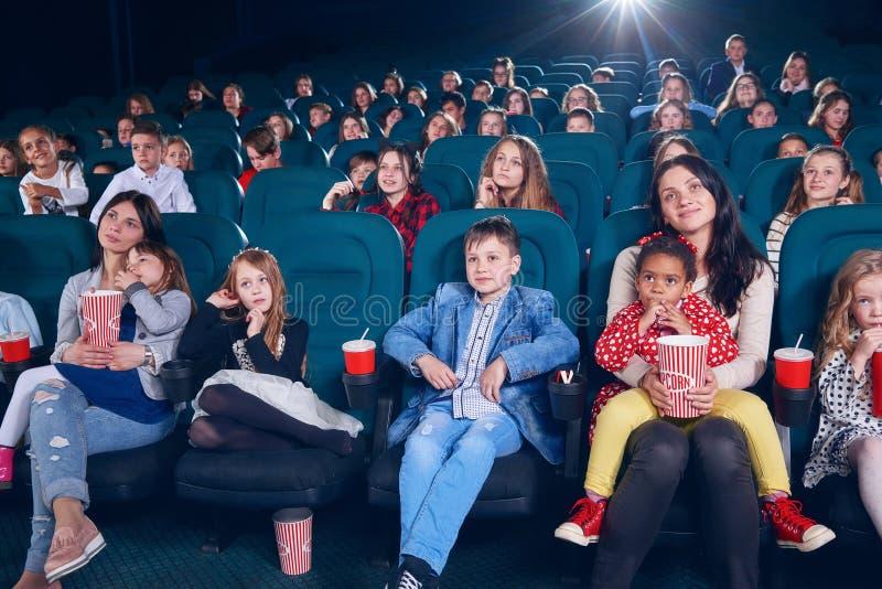 Moeder het letten op film met kleine kinderen op eerste bioskooprij royalty-vrije stock afbeeldingen