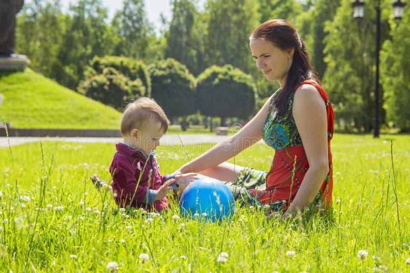 Moeder het spelen met haar baby op een grote zonnige dag in een weide met veel groen gras en wilde bloemen stock foto
