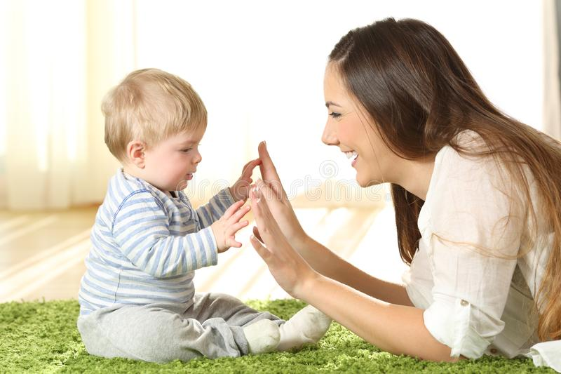 Moeder het spelen met haar baby op een tapijt stock foto