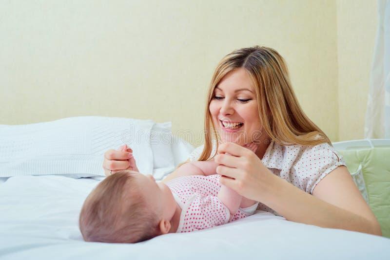 Moeder het spelen met haar baby op het bed Mammaglimlachen aan haar kind stock foto's