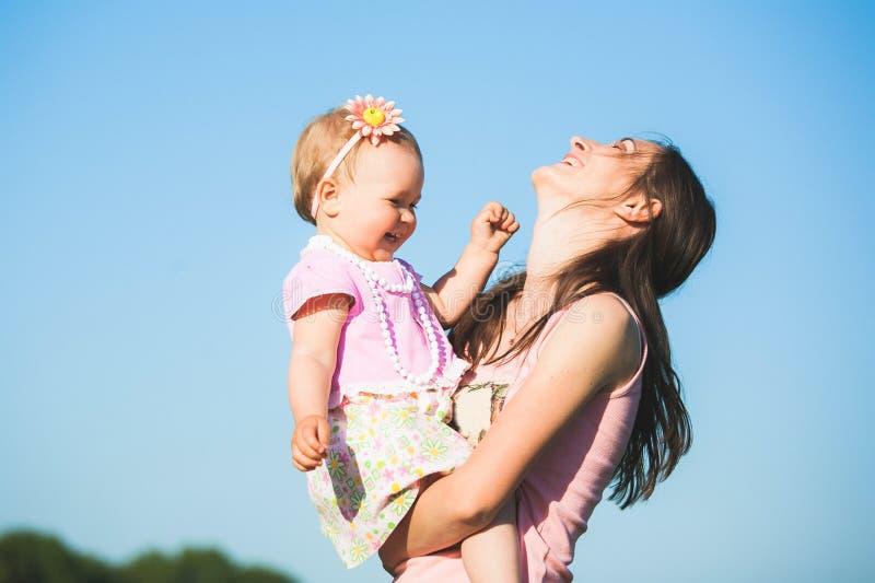 Moeder het spelen met haar kind buiten op zonnige warme dag stock afbeelding