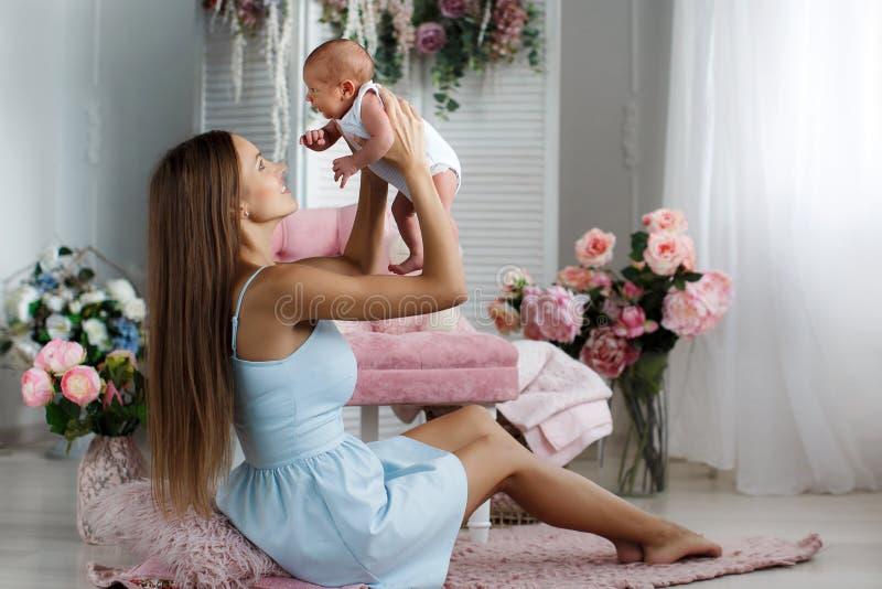 Moeder het spelen met pasgeboren babyzitting op de vloer stock foto's