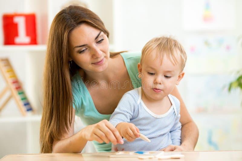 Moeder het spelen raadsel samen met haar zoon stock afbeelding