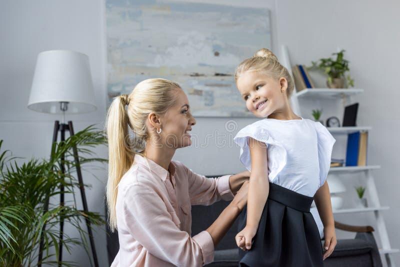 Moeder kledende dochter aan school stock foto's