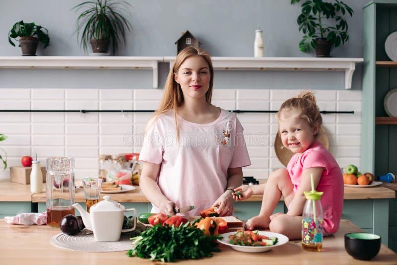 Moeder kokend diner op keuken met haar weinig leuk jong geitje royalty-vrije stock foto's