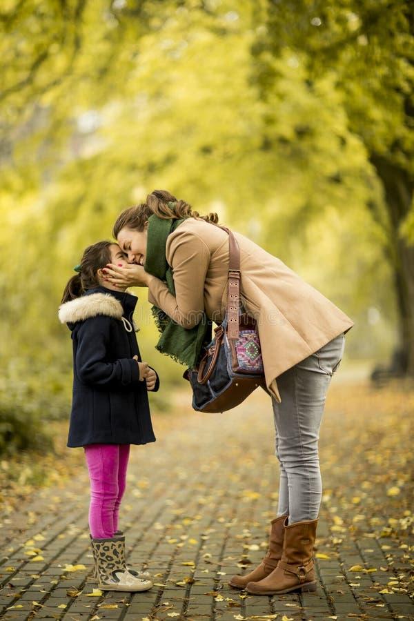 Moeder kussende dochter in het park stock fotografie