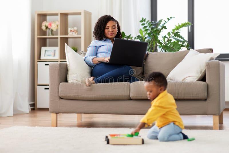 Moeder laptop met behulp van en baby die speelstuk speelgoed blokken royalty-vrije stock fotografie