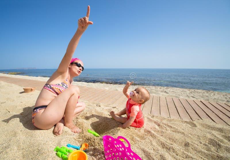 Moeder met baby bij de kust stock afbeelding