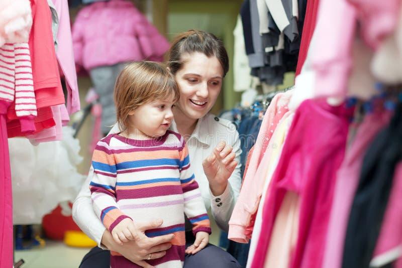 Moeder met baby bij klerenopslag stock afbeelding