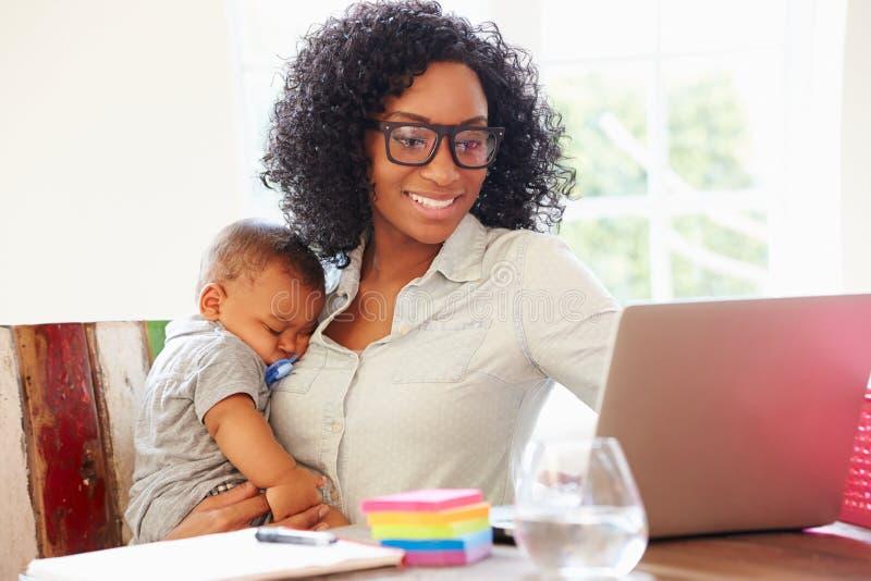 Moeder met Baby het Werken in Bureau thuis royalty-vrije stock afbeelding