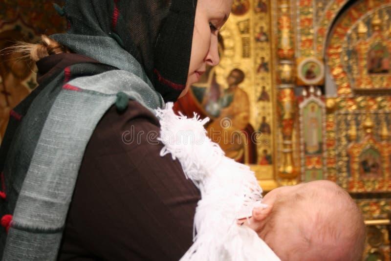 Moeder met baby in kerk stock fotografie