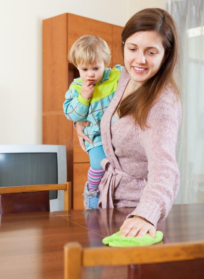 Moeder met baby schoonmakend huis stock foto