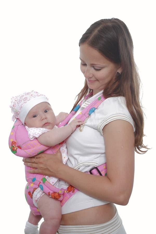 Moeder met baby in slinger stock afbeeldingen